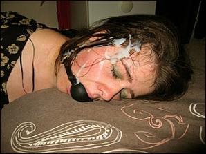 Afgeneukt ligt sletje onder het zaad met smoorbal in haar mond